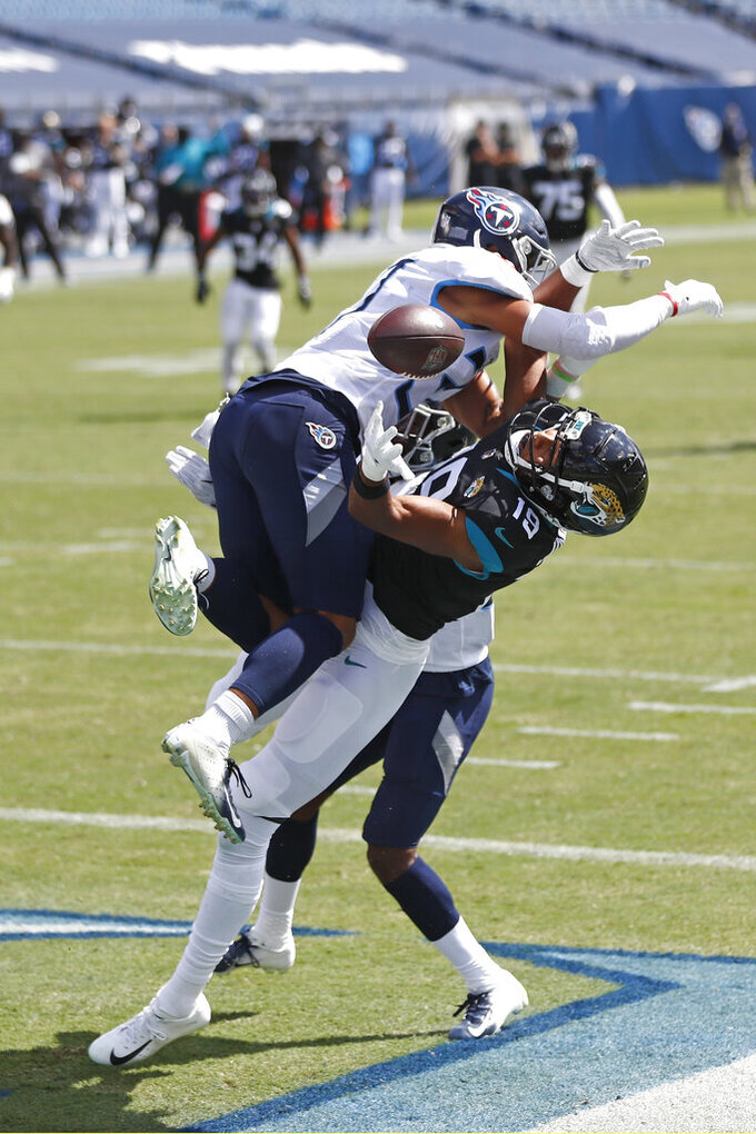 Jacksonville Jaguars wide receiver Collin Johnson (19) reaches for a pass under Tennessee Titans defenders Tennessee Titans safety Amani Hooker (37) in the first half of an NFL football game Sunday, Sept. 20, 2020, in Nashville, Tenn. The pass was incomplete. (AP Photo/Wade Payne)