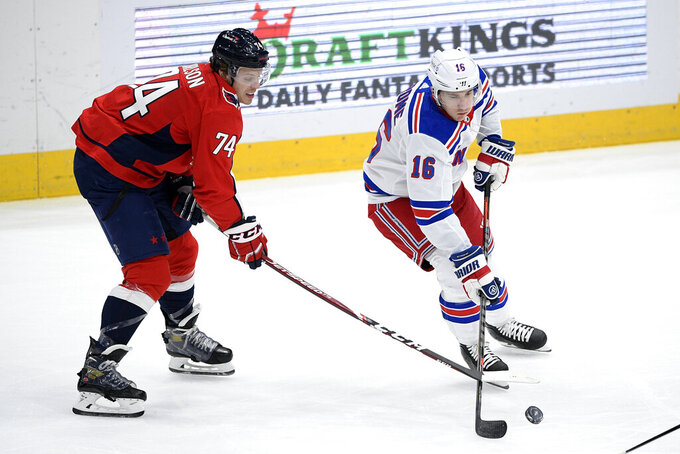 New York Rangers center Ryan Strome (16) and Washington Capitals defenseman John Carlson (74) reach for the puck during the first period of an NHL hockey game Friday, March 19, 2021, in Washington. (AP Photo/Nick Wass)