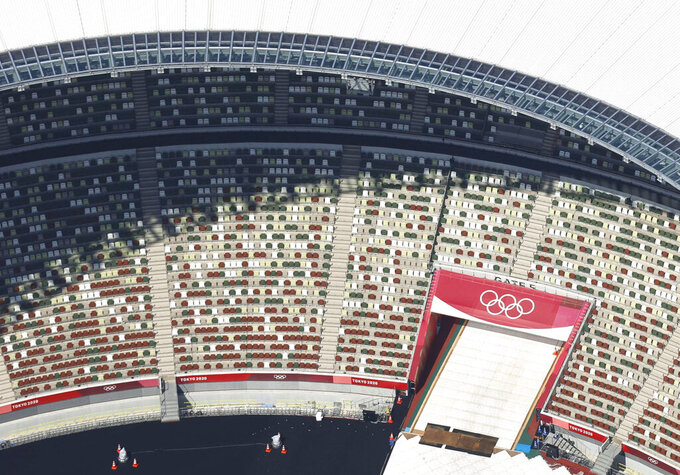FILE - In this aerial photo, the Olympic Rings are seen with spectators' seats at the National Stadium in Tokyo Japan, Monday, June 21, 2021. A state of emergency began Monday, July 12, 2021 in Tokyo, as the number of new cases is climbing fast and hospital beds are starting to fill just 11 days ahead of the Tokyo Olympics. (Kyodo News via AP, File)
