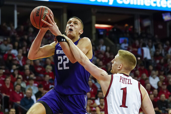 Wisconsin's Brevin Pritzl (1) fouls Northwestern's Pete Nance (22) during the first half of an NCAA college basketball game Wednesday, March 4, 2020, in Madison, Wis. (AP Photo/Andy Manis)