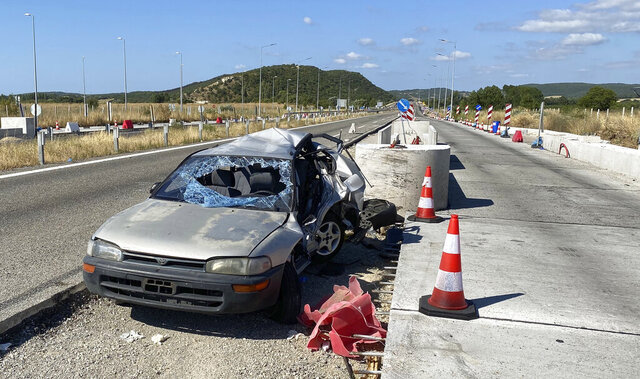 A damaged car sits in toll stations still under construction in the village of Ardanio, near Alexandroupolis town, northeastern Greece, Wednesday, Aug. 5, 2020. Police say the car believed to have been transporting migrants who recently illegally entered the country and crashed into roadworks on a highway overnight, killing seven people and injuring five. (e-evros.gr via AP)