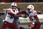 Nebraska quarterback Noah Vedral passes the ball off to running back Dedrick Mills during an NCAA college football game against Minnesota, Saturday, Oct. 12, 2019, in Minneapolis. (AP Photo/Stacy Bengs)