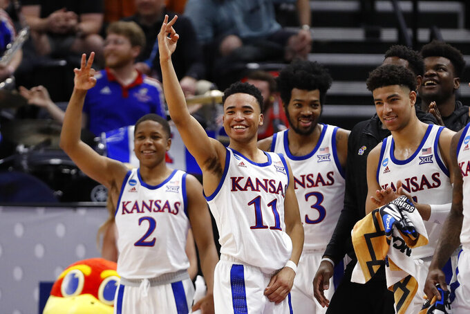 Kansas guard Charlie Moore (2), guard Devon Dotson (11), guard K.J. Lawson (13) and the rest of their bench celebrate a 3-pointer against Northeastern during the second half of a first-round game in the NCAA men's college basketball tournament Thursday, March 21, 2019, in Salt Lake City. (AP Photo/Jeff Swinger)