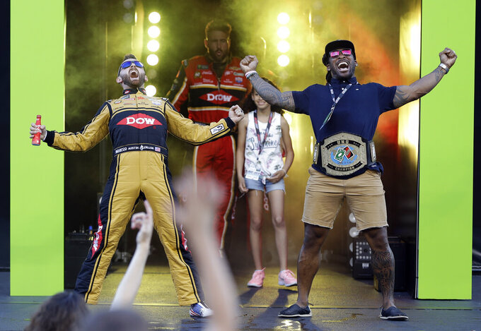 Austin Dillon, left, celebrates with former Carolina Panthers running back DeAngelo Williams during driver introductions for the NASCAR All-Star Race at Charlotte Motor Speedway in Concord, N.C., Saturday, May 18, 2019. (AP Photo/Chuck Burton)