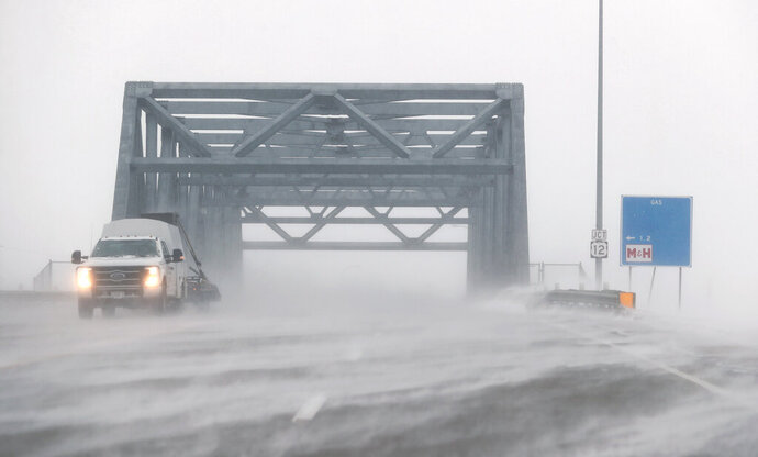 In this Wednesday, Feb. 12, 2020, photo, blowing snow moves over the roadway near the bridge on the U.S. Highway 281 bypass as blizzard and near white out conditions made travel in and around Aberdeen, S.D., difficult at times. (John Davis/Aberdeen American News via AP)