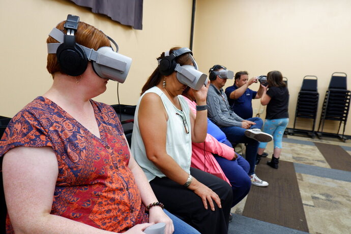 In this Sept. 6, 2019, photo provided by Ways of Knowing, audience members try out virtual reality headsets to watch