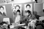 FILE - In this Nov. 5, 1979, file photo, Ebrahim Asgharzadeh, left, a representative of the Iranian students who stormed the U.S. Embassy on Nov. 4, holds up a portrait of one of the blindfolded hostages, during a news conference in the embassy in Tehran. Posters of the Islamic Revolution leader Ayatollah Ruhollah Khomeini adorn the wall. The man at right is unidentified. Speaking to The Associated Press ahead of the 40th anniversary of the attack, Asgharzadeh acknowledged that the repercussions of the crisis still reverberate as tensions remain high between the U.S. and Iran over Tehran's collapsing nuclear deal with world powers. (AP Photo/File)
