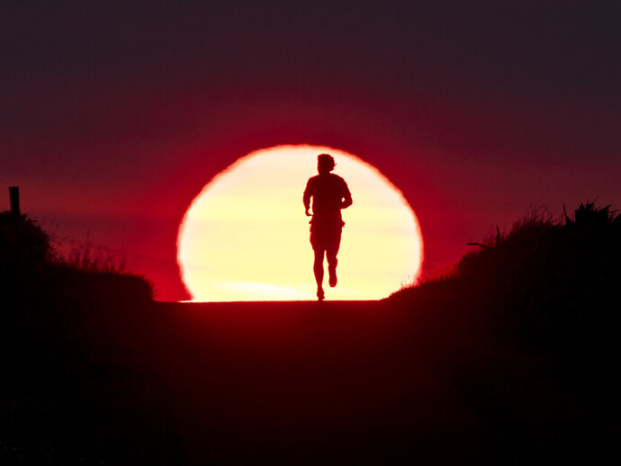 FILE - In this June 27, 2019 file photo a man runs on a small path as the sun rises in Frankfurt, Germany. The world could see average global temperatures 1.5 degrees Celsius (2.7 Fahrenheit) above the pre-industrial average for the first time in the coming five years, the U.N. weather agency said Thursday. The 1.5-C mark is a key threshold that countries have agreed to limit global warming to, if possible. Scientists say average temperatures around the world are already at least 1 C higher now than during the period from 1850-1900 because of man-made greenhouse emissions.  (AP Photo/Michael Probst, file)