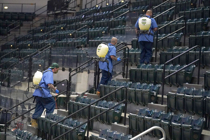 Workers at at Bankers Life Fieldhouse sanitize seats following a first-round game in the NCAA men's college basketball tournament, Friday, March 19, 2021, in Indianapolis. (AP Photo/Darron Cummings)