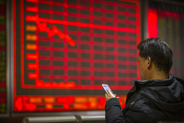 A Chinese investor uses his smartphone as he monitors stock prices at a brokerage house in Beijing, Friday, Jan. 10, 2020. Asian shares rose Friday as worries receded the United States and Iran might be stepping closer to the edge of war, and U.S. indexes hit records. (AP Photo/Mark Schiefelbein)