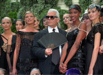 FILE - In this Tuesday July 9, 1996 file photo, Karl Lagerfeld is surrounded by Canadian model Linda Evangelista, left, and British model Naomi Campbell, right, and other models after the presentation of his 1996-97 fall-winter haute couture fashion collection for Chanel in Paris. Chanel's iconic couturier, Karl Lagerfeld, whose accomplished designs as well as trademark white ponytail, high starched collars and dark enigmatic glasses dominated high fashion for the last 50 years, has died. He was around 85 years old. (AP Photo/Lionel Cironneau, File)
