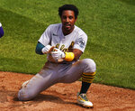 Oakland Athletics' Tony Kemp (5) reacts after avoiding the tag at home plate by Colorado Rockies third baseman Josh Fuentes (8) during the third inning of a baseball game, Wednesday, Sept. 16, 2020, in Denver. (AP Photo/Jack Dempsey)