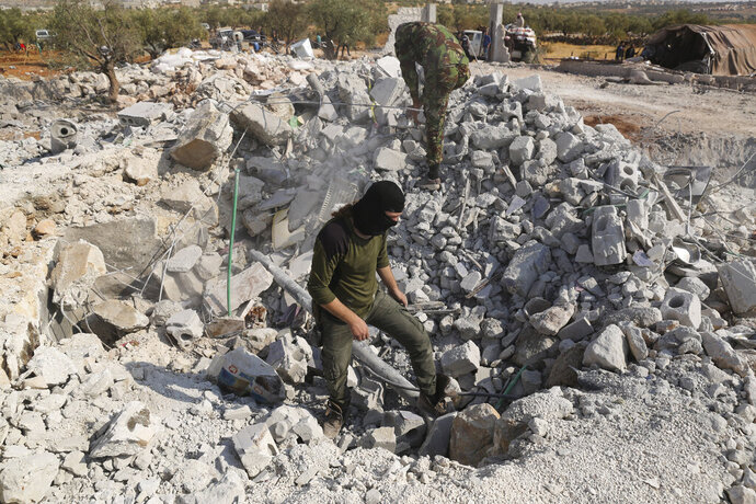 FILE - In this Oct. 27, 2019, file photo, people look at a destroyed houses near the village of Barisha, in Idlib province, Syria, after an operation by the U.S. military which targeted Abu Bakr al-Baghdadi, the shadowy leader of the Islamic State group. In his last months on the run, al-Baghdadi was agitated, fearful of traitors, sometimes disguised as a shepherd, sometimes hiding underground, always dependent on a shrinking circle of confidants. (AP Photo/Ghaith Alsayed, File)