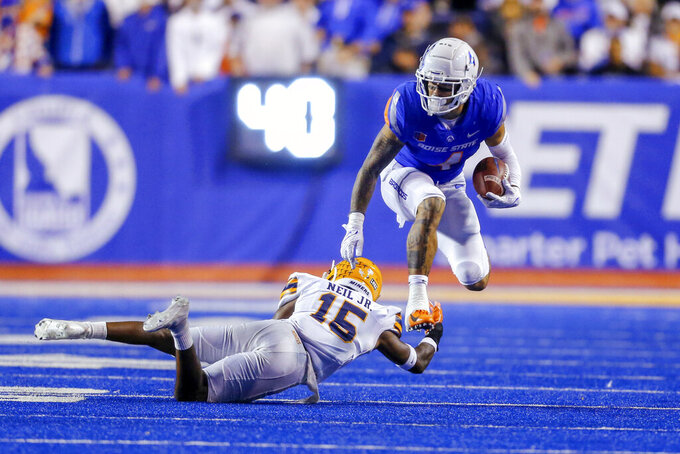Boise State running back Cyrus Habibi-Likio (4) jumps over the tackle attempt by UTEP cornerback Walter Neil (15) on a run during the second half of an NCAA college football game Friday, Sept. 10, 2021, in Boise, Idaho. (AP Photo/Steve Conner)