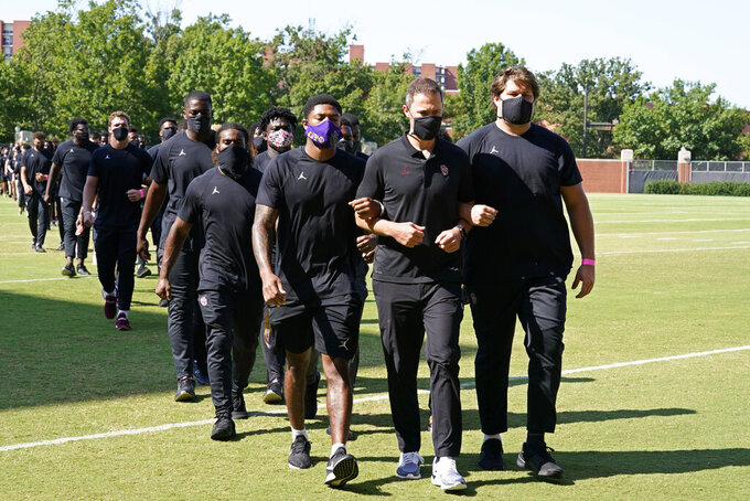 Chanse Sylvie, left, head coach Lincoln Riley, center, and Creed Humphrey, right, lead the Oklahoma football team back to the Gaylord Family – Oklahoma Memorial Stadium after a short campus march in Norman, Okla., Friday, Aug. 28, 2020. (AP Photo/Sue Ogrocki)
