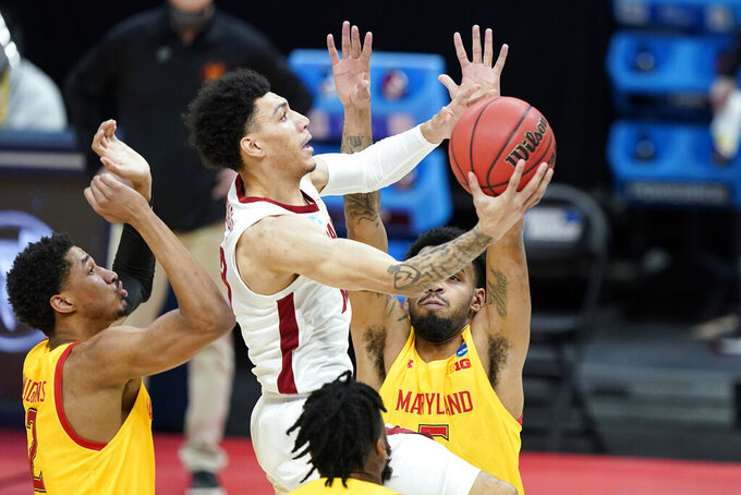 Alabama's Jahvon Quinerly, center, scores ahead of Maryland's Aaron Wiggins (2) and Eric Ayala, right, during the first half of a college basketball game in the second round of the NCAA tournament at Bankers Life Fieldhouse in Indianapolis Monday, March 22, 2021. (AP Photo/Mark Humphrey)