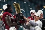 Alabama head coach Nick Saban and offensive lineman Alex Leatherwood hold the trophy after their win against Ohio State in an NCAA College Football Playoff national championship game, Tuesday, Jan. 12, 2021, in Miami Gardens, Fla. Alabama won 52-24. (AP Photo/Chris O'Meara)