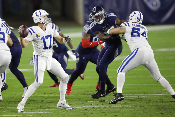 Indianapolis Colts quarterback Philip Rivers (17) passes as offensive guard Mark Glowinski (64) blocks Tennessee Titans linebacker Jadeveon Clowney (99) in the first half of an NFL football game Thursday, Nov. 12, 2020, in Nashville, Tenn. (AP Photo/Ben Margot)