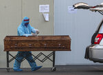 A funeral worker wearing protective gear as a precaution against the spread of the new coronavirus, sprays disinfectant on a coffin that contains the remains of person who died from the new coronavirus, at the San Jose hospital in Santiago, Chile, Tuesday, May 26, 2020. (AP Photo/Esteban Felix)