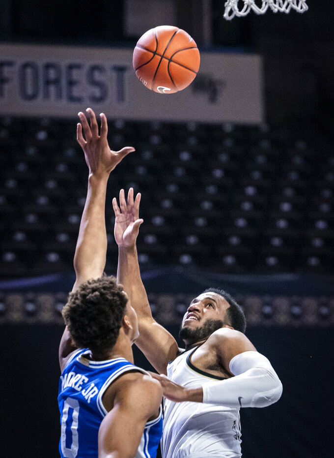 Wake Forest guard Ian DuBose (11) shoots over Duke forward Wendell Moore Jr. (0) during an NCAA college basketball game Wednesday, Feb. 17, 2021, in Wintson-Salem, N.C. (Andrew Dye/The Winston-Salem Journal via AP, Pool)