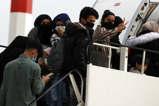 Migrants wearing face masks to prevent the spread of the coronavirus, board an airplane bound for Britain at the Eleftherios Venizelos International Airport in Athens, on Monday, May 11, 2020. Sixteen asylum-seeking minors and 34 migrants were relocated as part of a migrant reunification plan agreed between the two countries. (AP Photo/Thanassis Stavrakis)