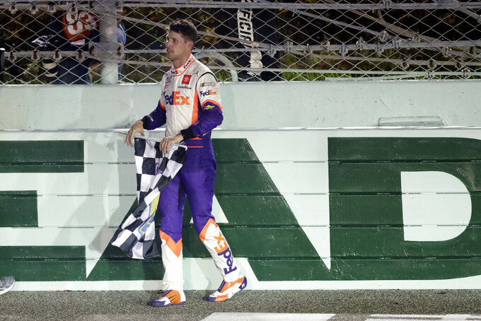 Denny Hamlin celebrates with the checkered flag after winning a NASCAR Cup Series auto race Sunday, June 14, 2020, in Homestead, Fla. (AP Photo/Wilfredo Lee)
