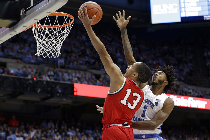 Ohio State guard CJ Walker (13) drives to the basket while North Carolina guard Leaky Black (1) defends during the second half of an NCAA college basketball game in Chapel Hill, N.C., Wednesday, Dec. 4, 2019. Ohio State won 74-49. (AP Photo/Gerry Broome)
