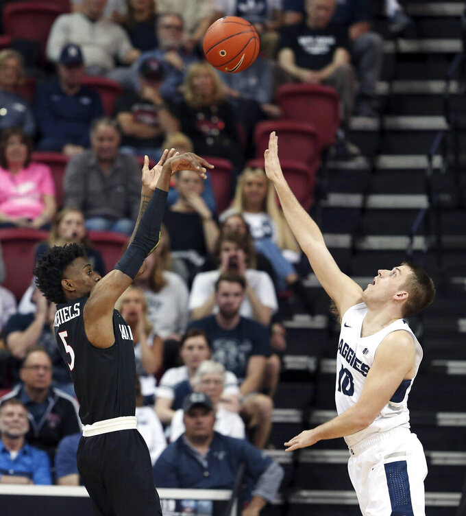 San Diego State's Jalen McDaniels shoots as Utah State's Quinn Taylor defends during the first half of an NCAA college basketball game in the Mountain West Conference men's tournament championship Saturday, March 16, 2019, in Las Vegas. (AP Photo/Isaac Brekken)