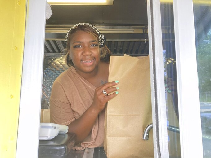 Yolanda Parson poses for a picture inside of her food truck, Crab Cravers, at its grand opening in Wilmington, Del., on Sunday, July 18, 2021. (José Ignacio Castañeda /The News Journal via AP)