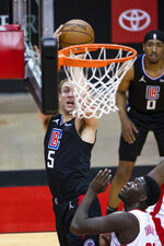 Los Angeles Clippers guard Luke Kennard (5) shoots over Houston Rockets forward Khyri Thomas (13) during the first quarter of an NBA game Friday, May 14, 2021, in Houston. (Mark Mulligan/Houston Chronicle via AP)