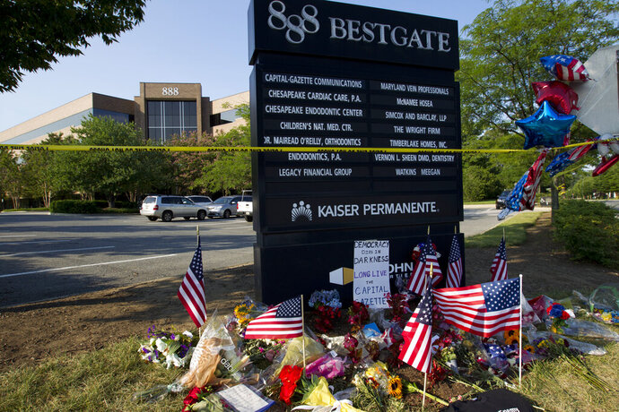 """FILE - In this July 1, 2018 file photo a makeshift memorial is seen at the scene outside the office building housing The Capital Gazette newspaper in Annapolis, Md.  Maryland is set to award $300,000 for the construction of a memorial honoring the victims of the 2018 shooting at the a newspaper office that killed five people. The Capital Gazette reports the state plans to award the funds next week for a memorial called """"Guardians of Free Speech."""