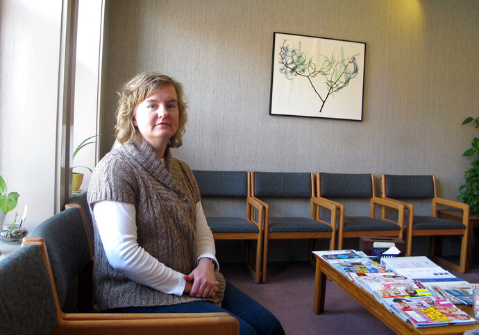 FILE - In this Feb. 20, 2013, file photo, Tammi Kromenaker, director of the Red River Valley Women's Clinic, North Dakota's sole abortion provider, sits in the waiting area of the facility in Fargo, N.D. A federal judge in North Dakota on Tuesday, Sept. 10, 2019, has blocked a state law passed earlier this year that required physicians to tell women they may reverse a so-called medication abortion if they have second thoughts. Kromenaker, said the law would force doctors to give false information that is not backed up by science. (AP Photo/Dave Kolpack, File)