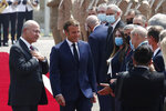 Iraqi President Barham Salih welcomes French President Emmanuel Macron, center, at the Salam Palace Wednesday, Sept. 2, 2020 in Baghdad. Macron is the first head of state to visit the Iraqi capital since Prime Minister Mustafa al-Kadhimi, Iraq's former intelligence chief, formed a new government in May. (Gonzalo Fuentes/Pool via AP)