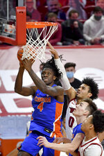 Florida forward Anthony Duruji (4) tries to drive past Arkansas defender Justin Smith (0) during the second half of an NCAA college basketball game in Fayetteville, Ark. Tuesday, Feb. 16, 2021. (AP Photo/Michael Woods)