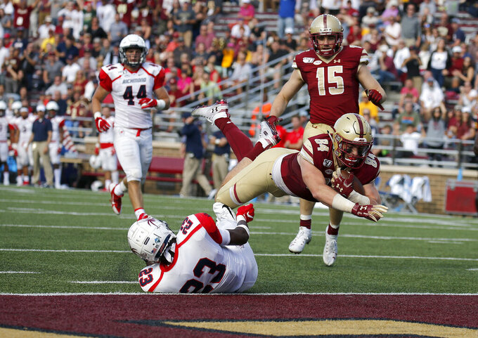 Boston College tight end Jake Burt (84) dives into the end zone for a touchdown over Richmond defensive back Daniel Jones (23) during the first half of an NCAA college football game, Saturday, Sept. 7, 2019, in Boston. (AP Photo/Mary Schwalm)