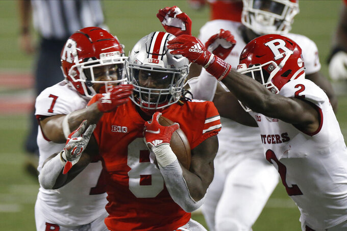 Ohio State running back Trey Sermon, center, is tackled by Rutgers defensive backs Brendon White, left, and Avery Young during the second half of an NCAA college football game Saturday, Nov. 7, 2020, in Columbus, Ohio. Ohio State won 49-27. (AP Photo/Jay LaPrete)