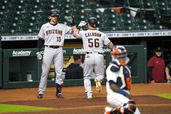 Arizona Diamondbacks' Kole Calhoun (56) celebrates with Nick Ahmed (13) after hitting a home run against the Houston Astros during the eighth inning of a baseball game Friday, Sept. 18, 2020, in Houston. (AP Photo/David J. Phillip)