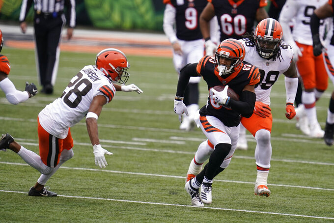 Cincinnati Bengals' Tyler Boyd (83) runs past Cleveland Browns' Kevin Johnson (28) during the second half of an NFL football game, Sunday, Oct. 25, 2020, in Cincinnati. (AP Photo/Michael Conroy)