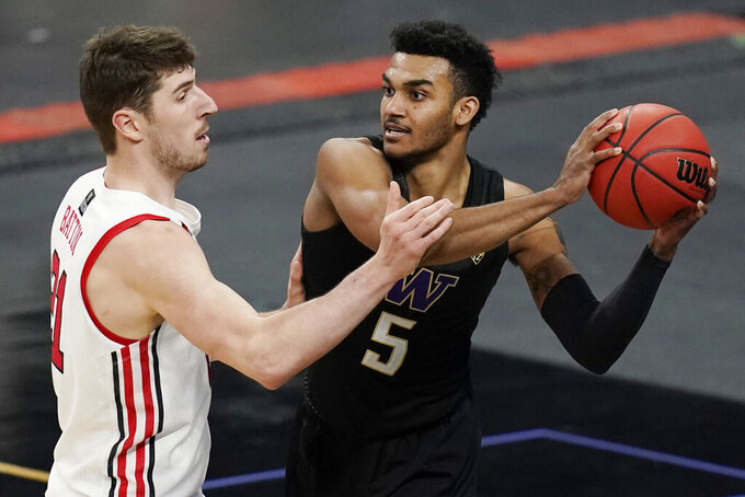 Washington's Jamal Bey (5) passes around Utah's Riley Battin (21) during the second half of an NCAA college basketball game in the first round of the Pac-12 men's tournament Wednesday, March 10, 2021, in Las Vegas. (AP Photo/John Locher)