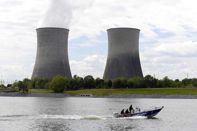 FILE - In this April 29, 2015 file photo, a boat travels on the Tennessee River near the Watts Bar Nuclear Plant near Spring City, Tenn. Federal regulators have fined the nation's largest public utility $145,000 for submitting incomplete and inaccurate information on a backup system at its Watts Bar Nuclear Plant. The Nuclear Regulatory Commission notified the Tennessee Valley Authority of the proposed fine regarding the Spring City, Tennessee plant in a Nov. 19, 2019 letter. The utility says it has taken corrective action, adding that the backup configuration was never used.  (AP Photo/Mark Zaleski, File)