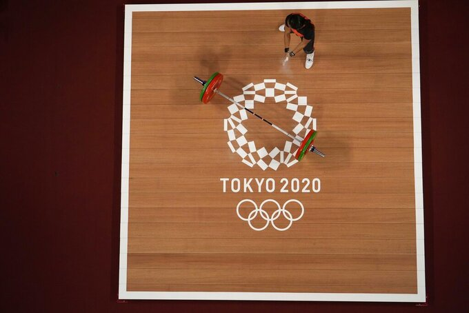 Loa Dika Toua of Papa New Guinea prepares to compete in the women's 49kg weightlifting event, at the 2020 Summer Olympics, Saturday, July 24, 2021, in Tokyo, Japan. (AP Photo/Luca Bruno)