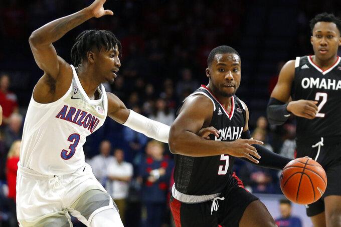 Omaha guard KJ Robinson (5) drives on Arizona guard Dylan Smith in the first half during an NCAA college basketball game, Wednesday, Dec. 11, 2019, in Tucson, Ariz. (AP Photo/Rick Scuteri)
