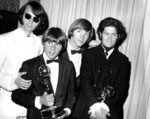 FILE - This June 4, 1967 file photo shows, from left, Mike Nesmith, Davy Jones, Peter Tork, and Micky Dolenz of The Monkees posing with their Emmy award for best comedy series at the 19th Annual Primetime Emmy Awards in Los Angeles.  Tork, who rocketed to teen idol fame in 1965 playing the lovably clueless bass guitarist in the made-for-television rock band The Monkees, died Thursday, Feb. 21, 2019, of complications related to cancer, according to his son Ivan Iannoli. He was 77.  (AP Photo, File)
