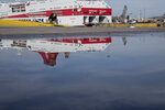 A man speaking on his mobile phone is reflected in a puddle during a 24-hour labor strike at the port of Piraeus, near Athens, Wednesday, June 16, 2021. Greece's biggest labor unions staged a 24-hour strike to protest a labor bill being voted in parliament. (AP Photo/Petros Giannakouris)