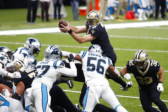 New Orleans Saints quarterback Drew Brees (9) dives over the pile for a touchdown in the first half of an NFL football game against the Carolina Panthers in New Orleans, Sunday, Oct. 25, 2020. (AP Photo/Brett Duke)