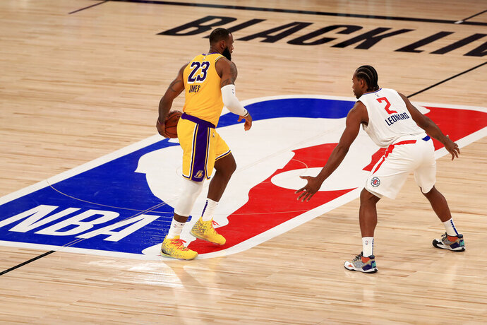 Los Angeles Lakers LeBron James (23) dribbles the ball against Los Angeles Clippers Kawhi Leonard (2) during the third quarter of an NBA basketball game Thursday, July 30, 2020, in Lake Buena Vista, Fla. (Mike Ehrmann/Pool Photo via AP)