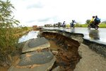Motorcycles pass through a section of road damaged by Cyclone Idai in Nyamatanda about 50 kilometres from Beira, in Mozambique, Thursday March, 21, 2019. Some hundreds are dead, many more still missing and thousands at risk from massive flooding across the region including Mozambique, Malawi and Zimbabwe caused by Cyclone Idai. (AP Photo/Tsvangirayi Mukwazhi)