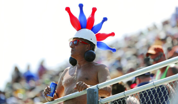 A fan with a balloon hat watches the NASCAR Cup Series auto race at Watkins Glen International, Sunday, Aug. 4, 2019, in Watkins Glen, N.Y. (AP Photo/John Munson)