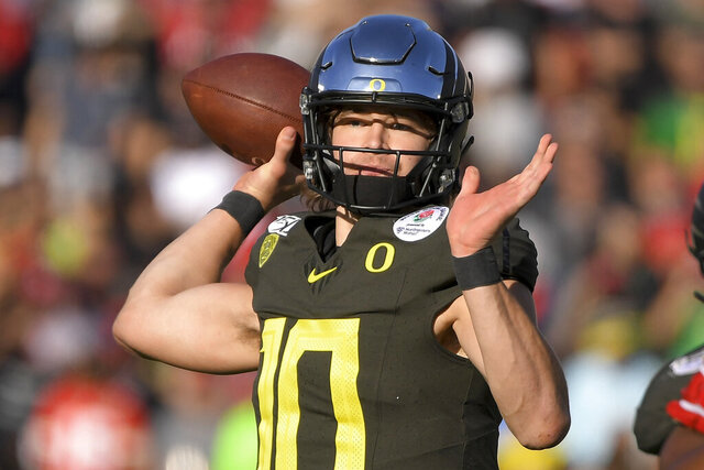 FILE - In this Jan. 1, 2020, file photo, Oregon quarterback Justin Herbert passes against Wisconsin during first half of the Rose Bowl NCAA college football game in Pasadena, Calif. Herbert is a likely first-round pick in the NFL draft Thursday, April 23, 2020. (AP Photo/Mark J. Terrill, File)