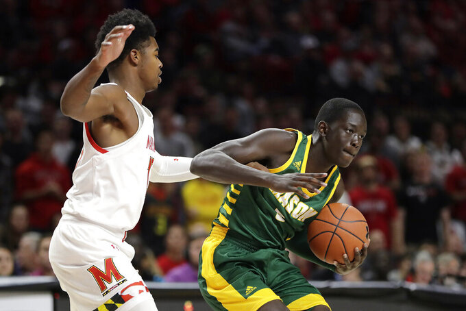 George Mason forward Goanar Mar, right, tries to control the ball while Maryland guard Hakim Hart defends during the first half of an NCAA college basketball game Friday, Nov. 22, 2019, in College Park, Md. (AP Photo/Julio Cortez)